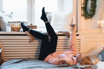 Deurstickers Ontspanning Coquette young girl having fun, making selfie while lying on the bed at home, near the window,