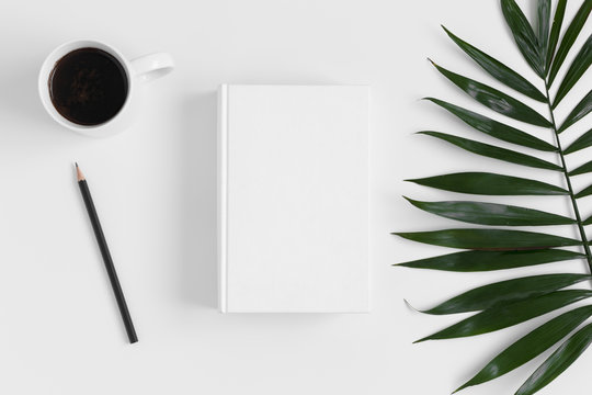 Top view of a white book mockup with  workspace accessories and a palm leaf on a white table.