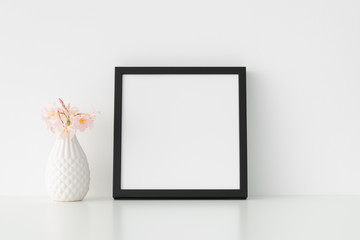 Black square frame mockup with pink oleander in a vase.