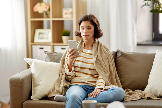 technology, health and cold concept - sad sick woman in blanket using smartphone at home
