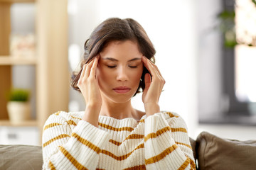 people , health and stress concept - unhappy woman suffering from head ache at home
