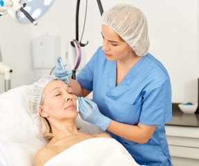 Senior woman getting injection for facial rejuvenation procedure in esthetic clinic
