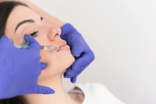 Woman having lower lip filler