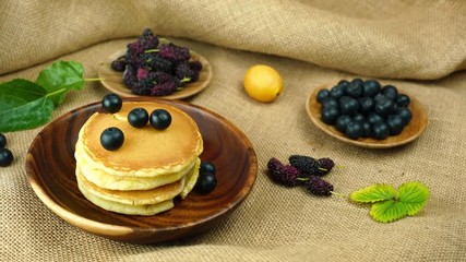 Fototapete - Pile of pancake in wooden bowl with marian plum, mulberry and blueberry in wooden plate on sackcloth