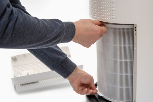 A man's hand turning an air purifier's filter into a new one.
