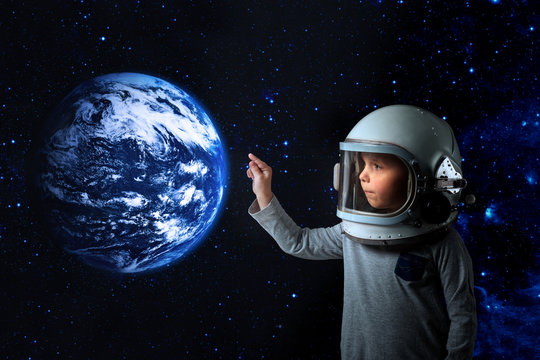 a small child imagines himself to be an astronaut in an astronaut's helmet.