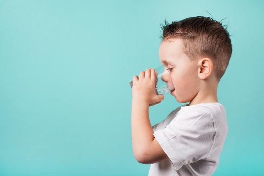 child drinks water on a turquoise background