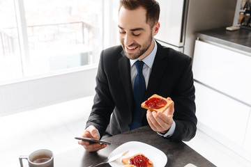 Image of smiling businessman having breakfast while using smartphone and working on laptop in bright apartment