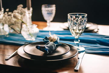This photo shows a wedding, festive table. Wedding decorations. Wedding table setting. Beautiful glasses and dishes