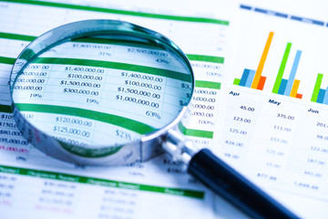 Magnifying glass on charts graphs spreadsheet paper. Financial development, Banking Account, Statistics, Investment Analytic research data economy, Stock exchange trading, Business office company