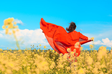 A young woman in a bright red dress dances and runs around the spring blooming field under the blue sky.
