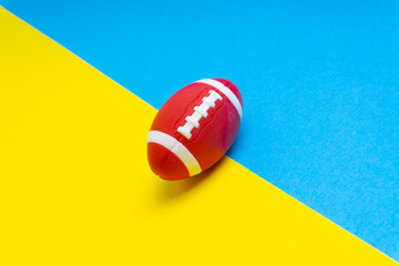Rugby ball on blue and yellow background. Selective focus