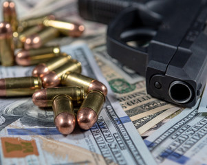 Firearm with ammunition on a background of United States currency. Selective focus