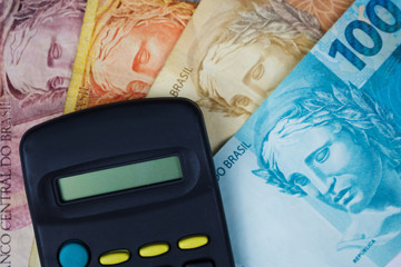 Brazilian money and calculator on a table. Economy concept image