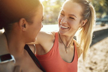 Wall Mural - Two young women in sportswear laughing after an outdoor workout