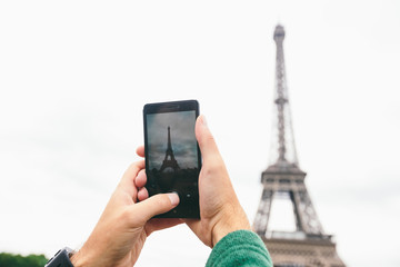 Hands Caucasian male tourist blogger makes the most important sights Paris France Eiffel Tower photo using smartphone