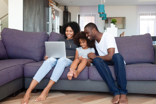 Happy African American family with daughter using laptop at home