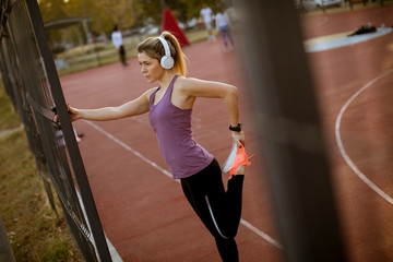 Pretty young woman stretching during sport training