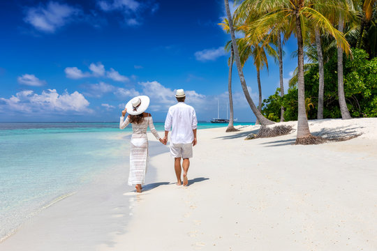Elegant traveler couple walks down a tropical beach with coconut palm trees and turquoise waters in the Maldives islands