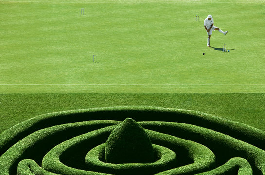 Man Playing Croquet On Manicured Lawn