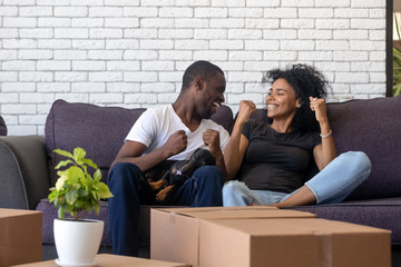 Excited African American couple in love celebrating moving day