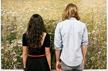 Couple Standing In Front Of Photograph