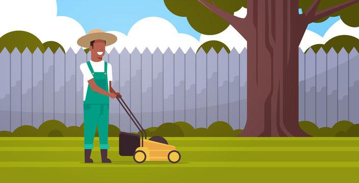 man gardener cutting green grass with lawn mover african american farmer moving garden backyard gardening concept flat full length horizontal
