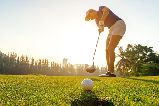 Sport Healthy. Golfer asian sporty woman focus putting golf ball on the green golf on sun set evening time.  Healthy and Lifestyle Concept