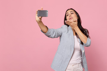 Tender young woman in striped jacket blowing sending air kiss, doing selfie shot on mobile phone isolated on pink pastel wall background. People sincere emotions lifestyle concept. Mock up copy space.