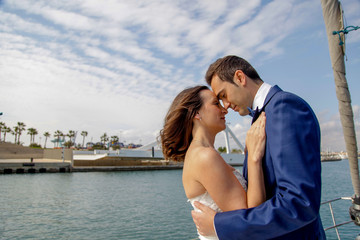 A couple of newly married lovers sail on a sailboat in a romantic attitude