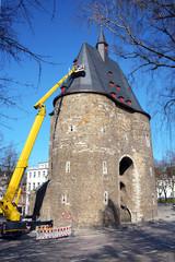 Dachdecker auf Hebebühne untersucht Dacharbeiten mit Schieferplatten als Dachziegel auf Turm von Stadttor, im besonderen dem Marschiertor in Aachen, Deutschland