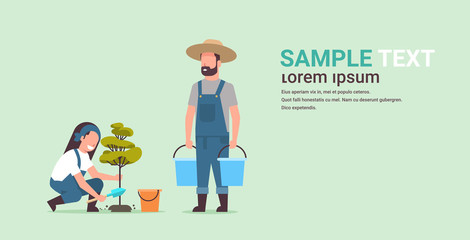couple farmers planting young tree man holding water buckets woman digging soil working in garden agricultural gardening concept flat full length copy space horizontal