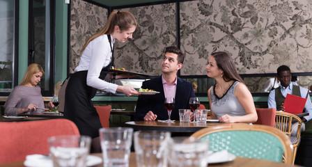 Waitress bringing dishes to couple