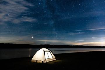 Zelten am See unter freiem Himmel, der voller Sterne die Milchstraße aufzeigt
