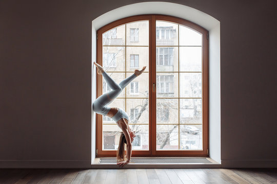 Beautiful young woman fitness model doing a difficult handstand in the gym. Concept of regular training and willpower. Advertising space