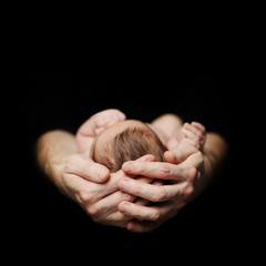 Parenthood concept. Newborn baby on father's hand on black background