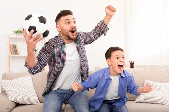 Father and son soccer fans cheering with football ball