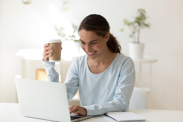Woman at work typing message on laptop smiling