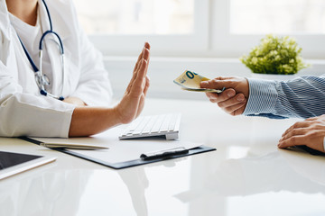Young female doctor refuses a bribe from her patient in medical office
