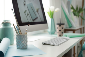 Stylish workplace with modern computer on desk. Focus on pencil holder Wall mural