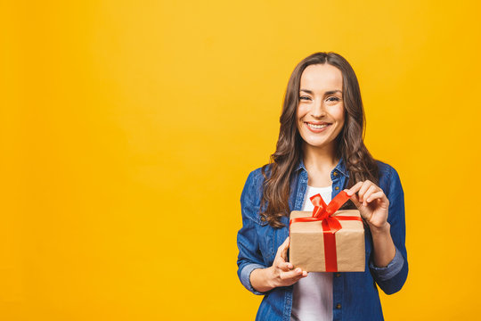 Smiling young beautiful woman holds red gift box. Isolated over yellow background. Studio.