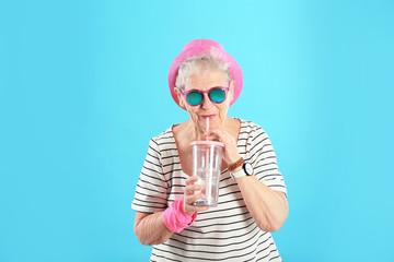 Portrait of cool grandmother with drink on color background Fotoväggar