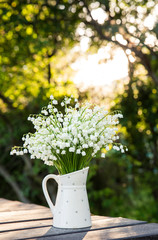 Bouquet of white flowers Lily of the valley (Convallaria majalis) also called: May bells, Our Lady's tears and Mary's tears in a white dotted jug shaped vase, outdoors on a table, trees on background.