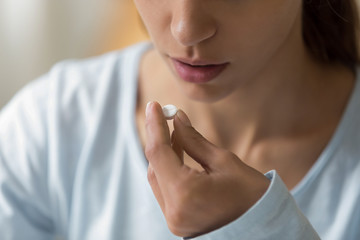 Closeup image of woman face and pill in hand
