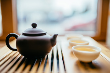 Teapot and cups with chinese tea near window on the table for the tea ceremony
