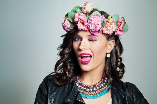 Happy fashion model woman winking. Pretty girl in flower crown portrait