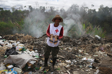 Venezuelan Oriana Padilla holds a bag of cans after scraping on a garbage dump in the border city of Pacaraima