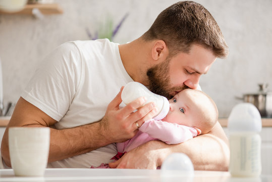 Young father kiss his baby during drinking milk