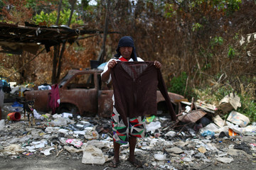 Venezuelan Euclide Mata holds a sweater after scraping on a garbage dump in the border city of Pacaraima