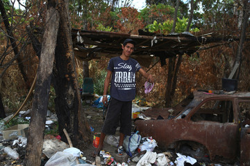 Venezuelan Frelvi Arteaga holds a pair of sandals after scraping on a garbage dump in the border city of Pacaraima